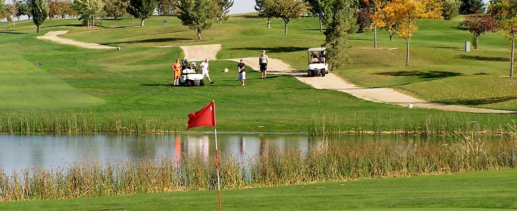 Golfers making shot to green