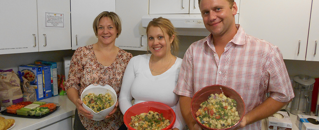 Three Allied Employees in Kitchen holding the food they made