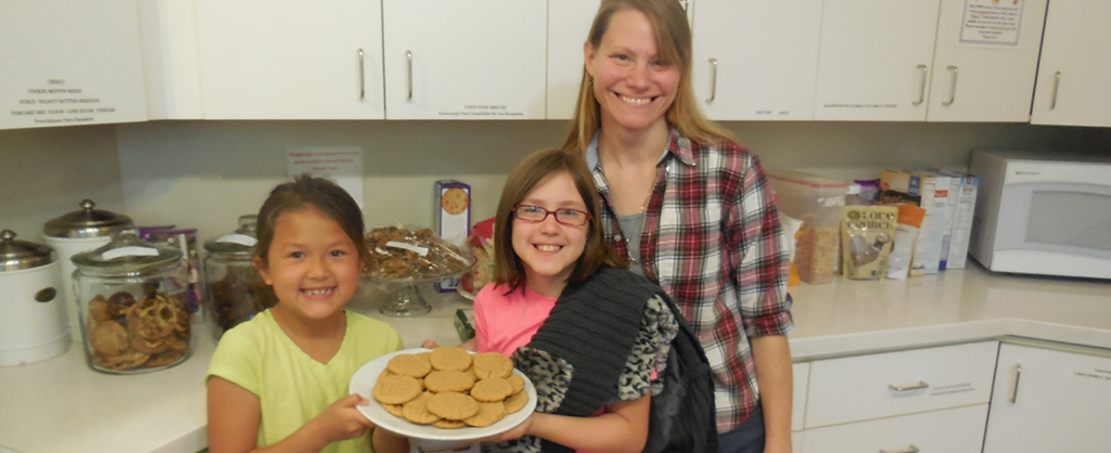 Mom with two girls in the kitchen holding a plate of cookies