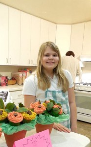 Young girl standing with cupcakes she made