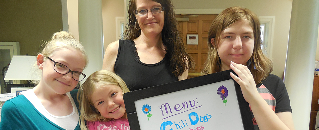 Mom and her three daughters holding the menu sign