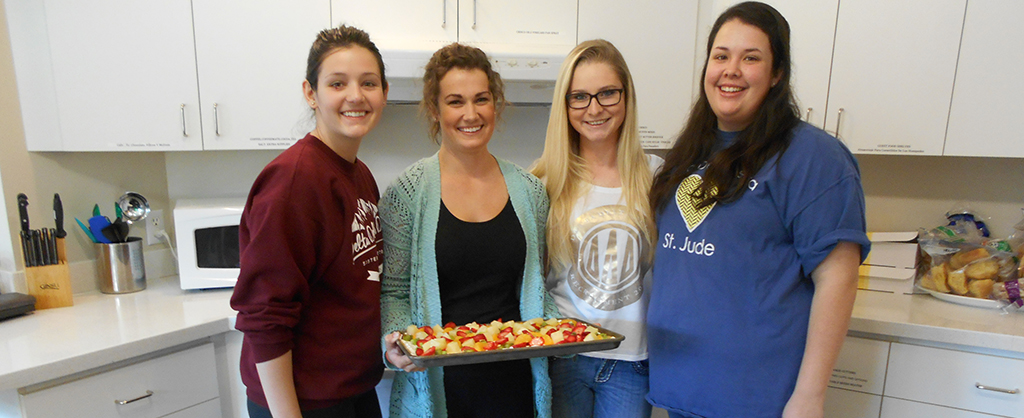 A group of from Tri Delta in the kitchen, holding the treats they made