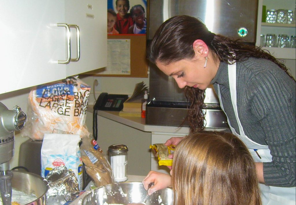 woman and child mixing ingredients in a large bowl
