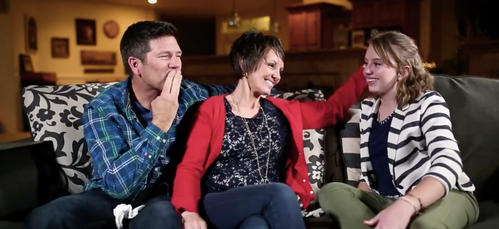 Mother and father looking at their daughter on a couch
