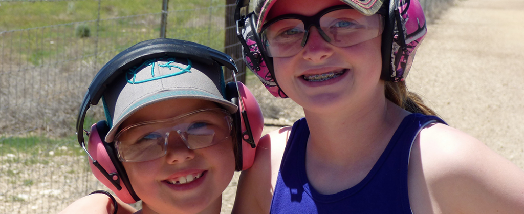Two young girls smile for the camera at the 15th annual sporting clays tournament out at Black Dog Clays.