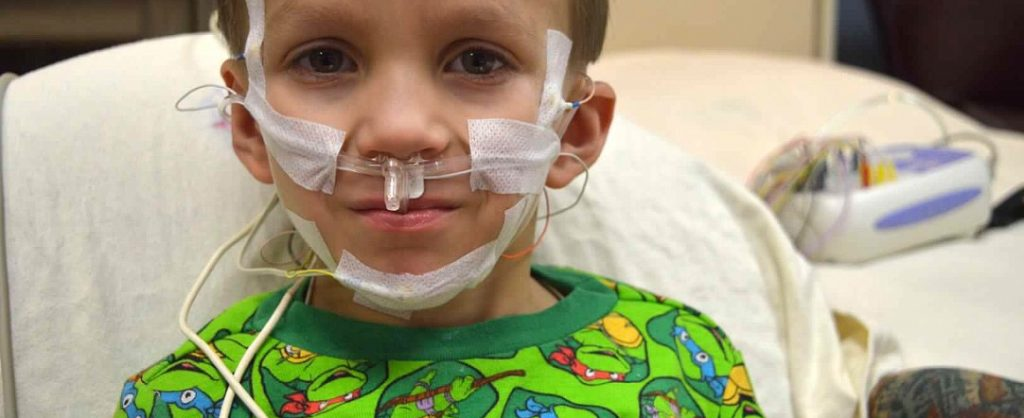 Young boy wearing ninja turtles shirt looks into camera while hooked up to tubes in the hospital.