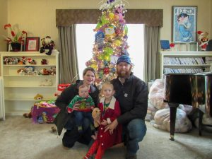 Family of four kneels and smiles in front of a christmas tree