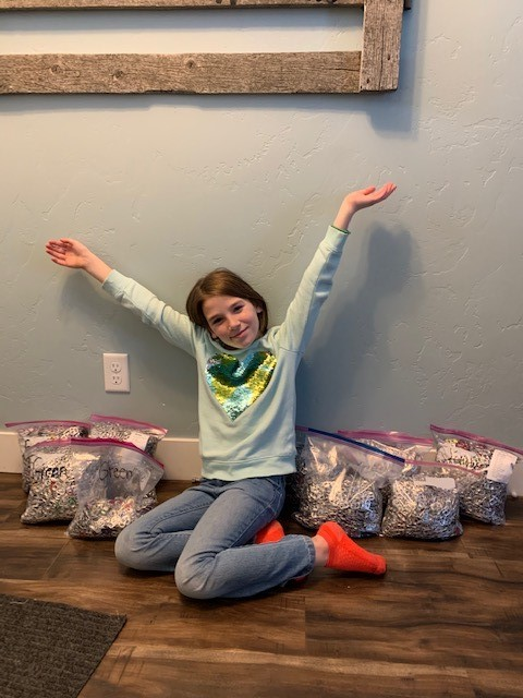 Young girl sits on the floor with hands up surrounded by bags of pull tabs she collected for RMHC.